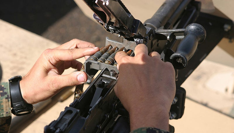 A Marine inserts an ammunition belt into the feed tray of the M240.