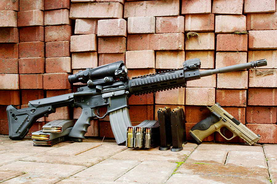 This is the author's personal defense rifle, a variation on the M-4 rifle that he built. It has a 3X Trijicon ACOG as the primary sight, with a red-dot reflex sight on an offset mount for close work.