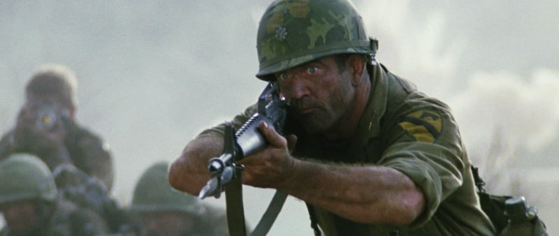 Gibson as Lt. Col. Hal Moore in *We Were Soldiers* charging with his XM15E1 rifle, bayonet fixed.