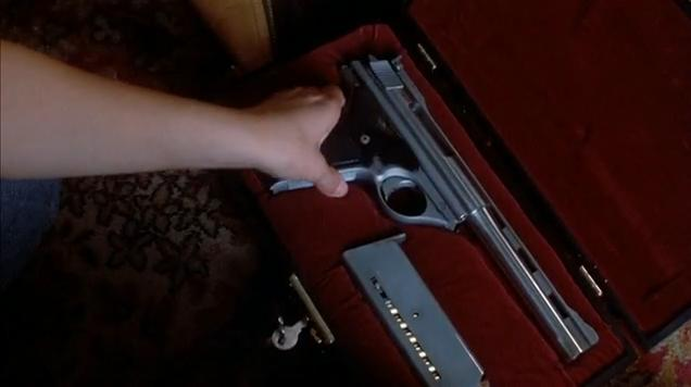 Jo finds the Automag under Malone's bed in its case.