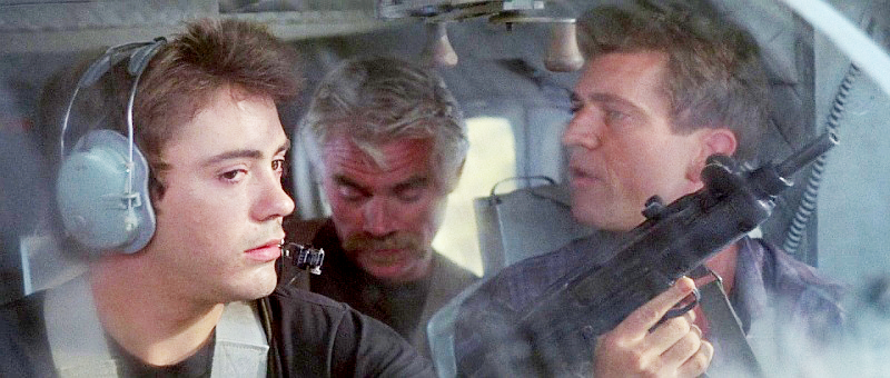 Gibson with an Uzi as a CIA pilot in *Air America* next to a young Robert Downey Jr.