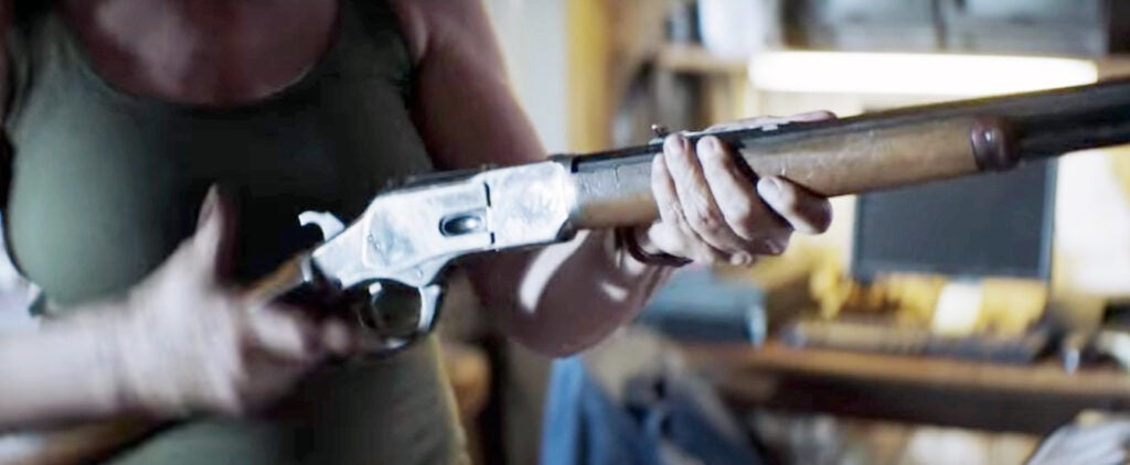 Laurie also cleans and loads her lever gun, which looks to be a Winchester 1873 variant.
