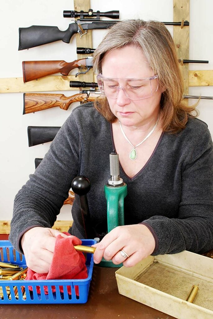 woman cleaning and inspecting cartridge cases