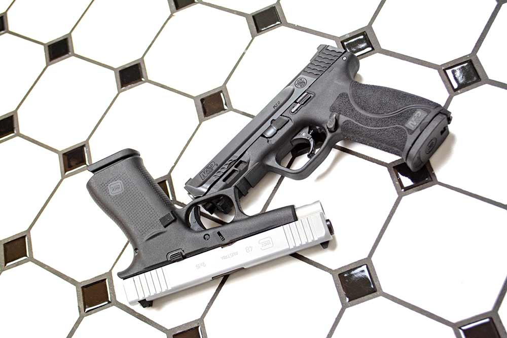 two handguns on a black and white checkered tile floor