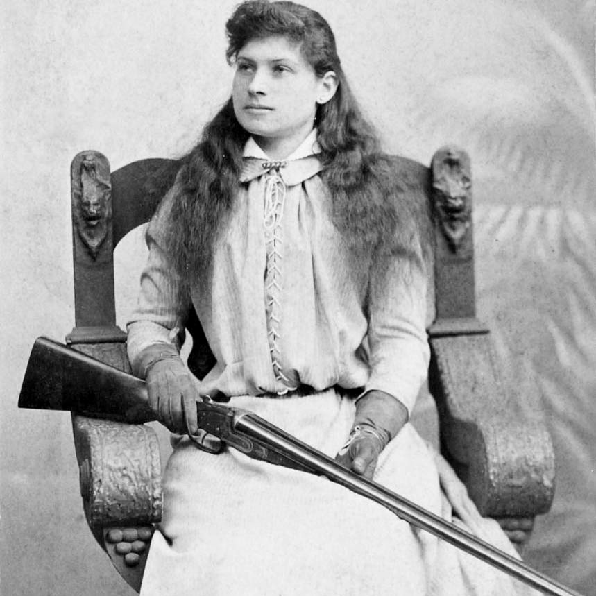 annie oakley sitting in a chair with a rifle in her lap