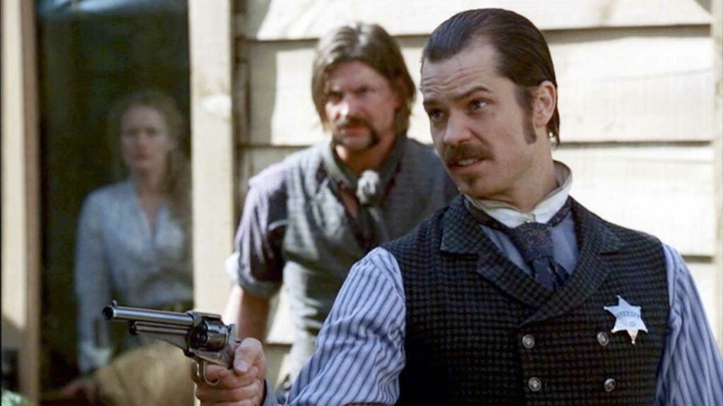 deadwood scene with seth bullock holding a remington model 1875