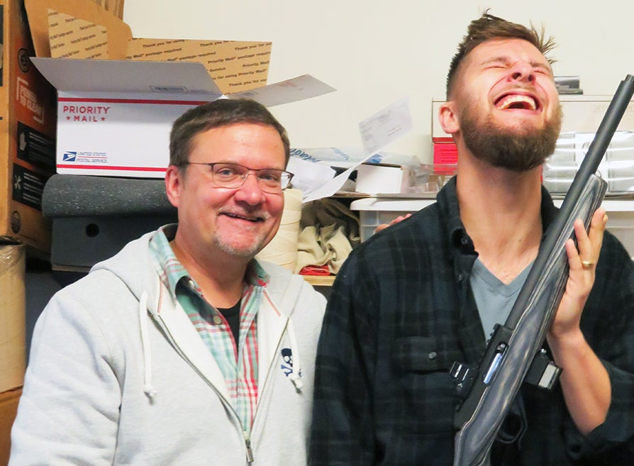 father and son holding new rifle