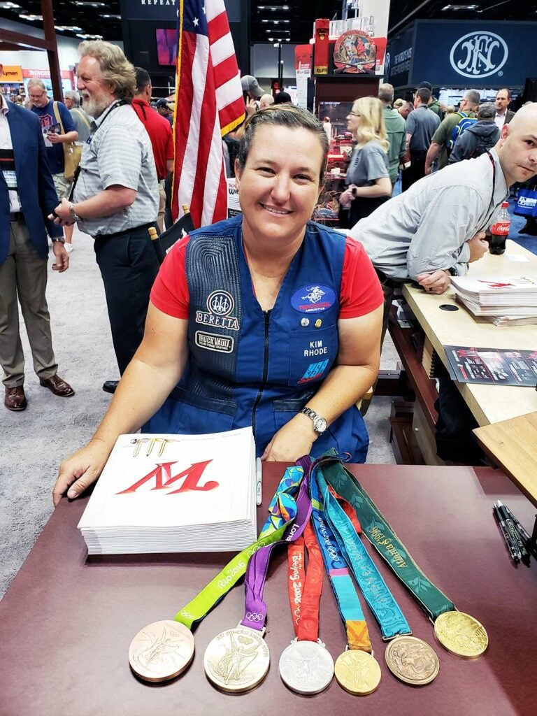 kim rhode at shot show with her shooting trophy medals in front of her