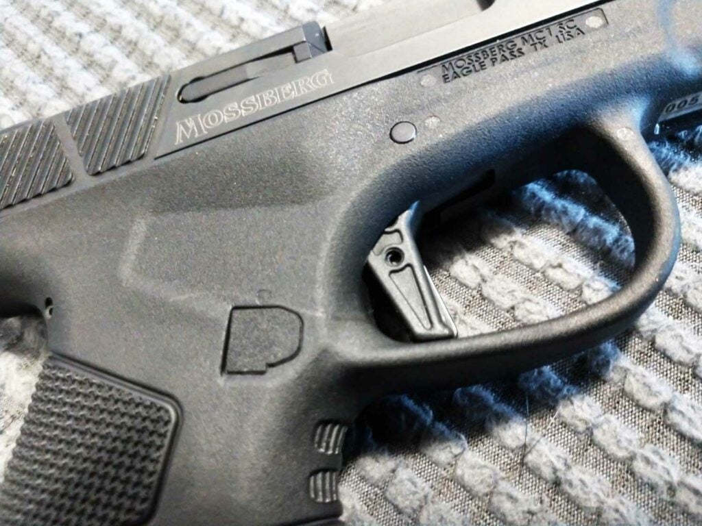 close up details of a flat trigger on the mossberg pistol