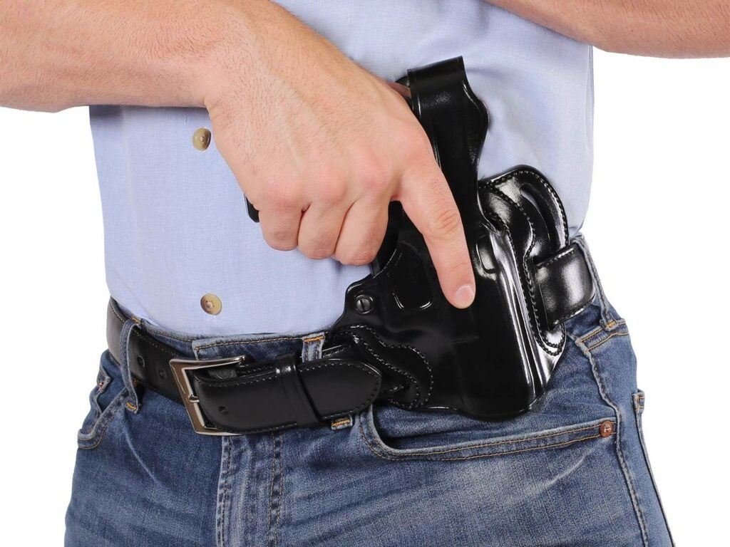 man cross drawing a gun in a concealed carry holster