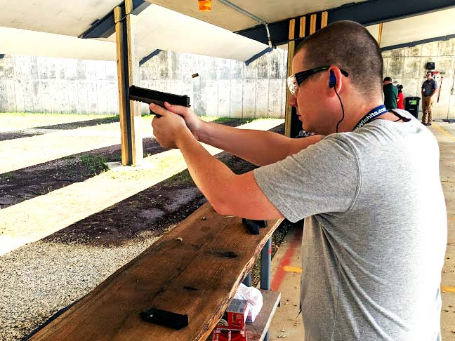 author aiming and firing pistol at a shooting range