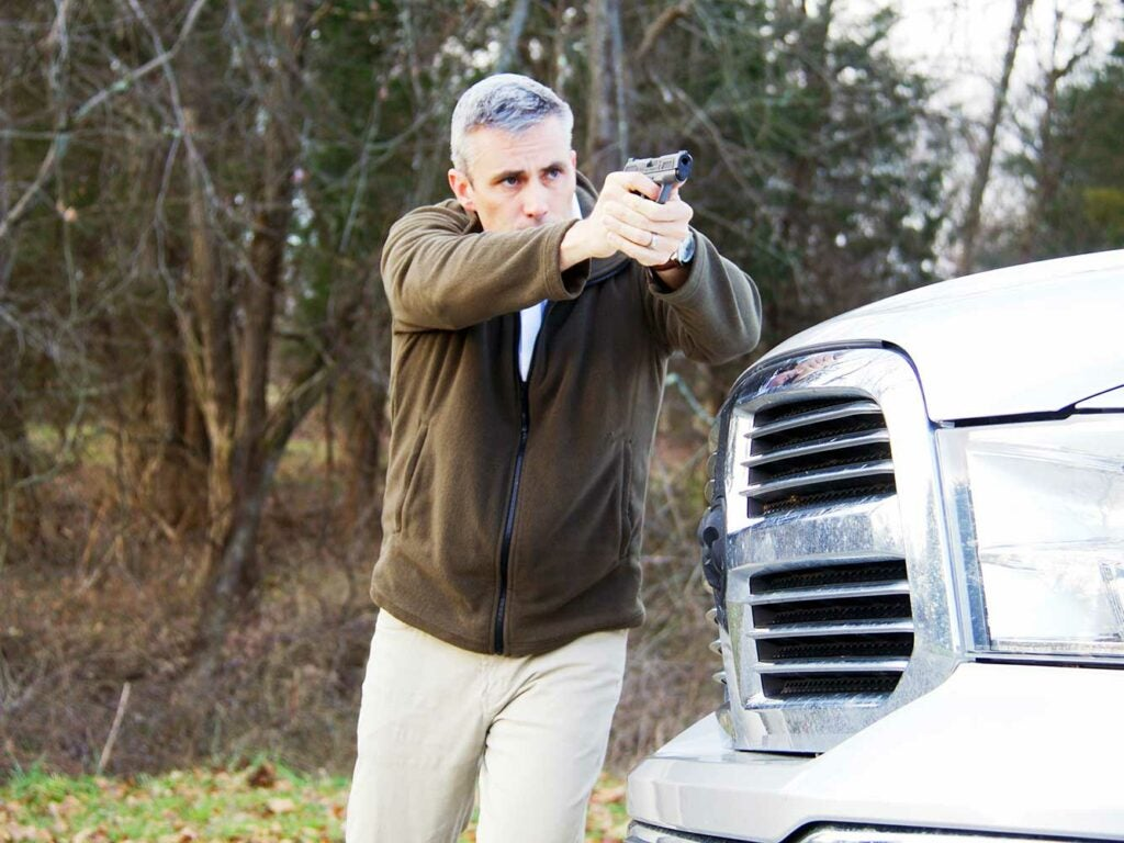 man aiming handgun in front of a white truck