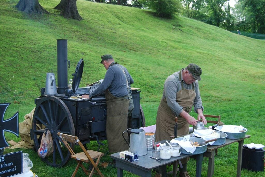 two men in a kitchen at a german army reenactment