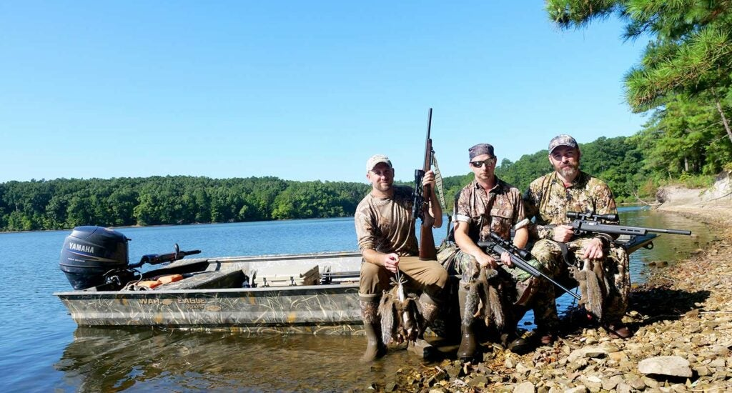 Hunters sitting on a boat while squirrel hunting.