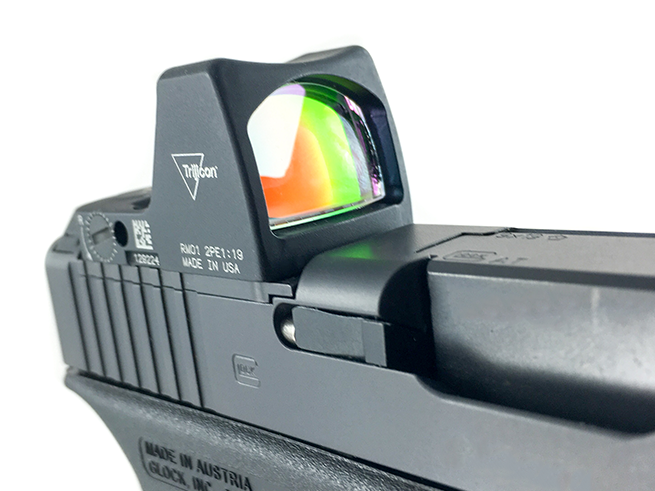 handgun equipped with modern red dot sights.