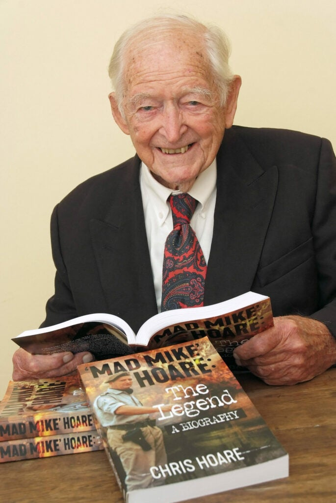 An aged Mike Hoare with a book about his life.