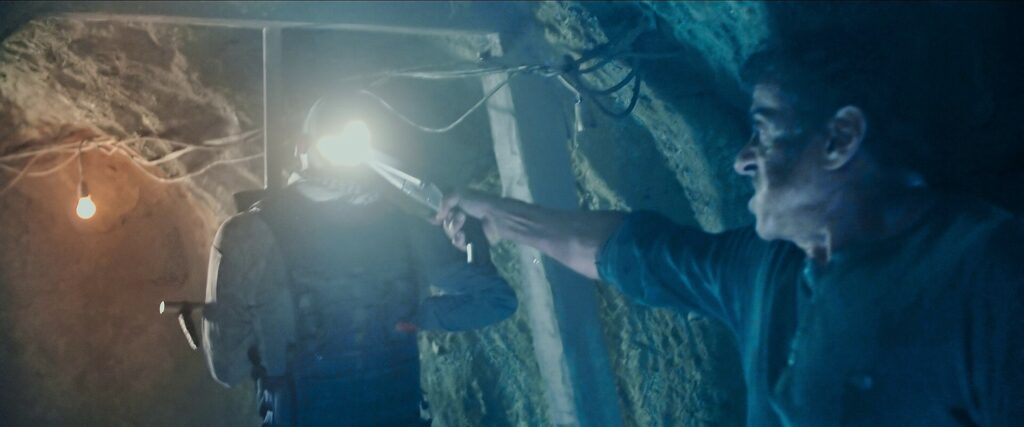 Rambo fires a sawed-off double barrel at a cartel member impaled on one of his booby traps in the tunnels.