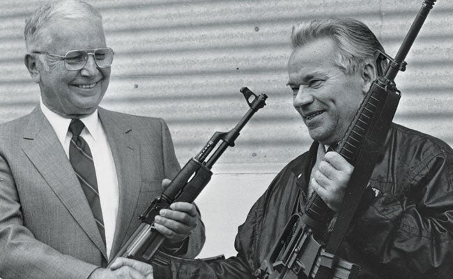 Eugene Stoner (left) and Mikhail Kalashnikov holding each other's incredibly impactful rifle designs, the AK-47 and the AR-15, respectively.