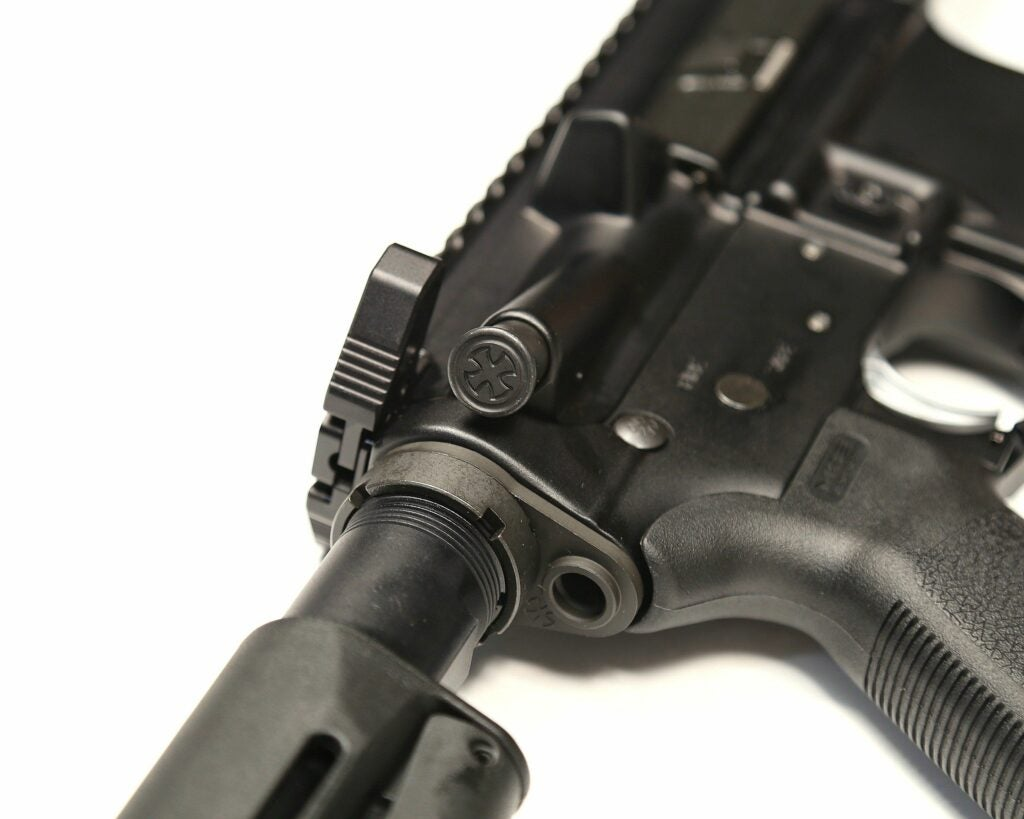 A Noveske forward assist on an AR-15 rifle.
