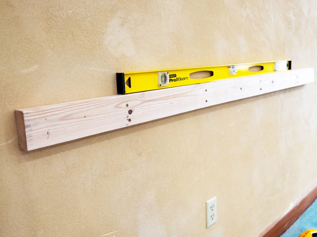 Attach the 2x4 to the wall on center at whatever height your black pipe legs measure out at.