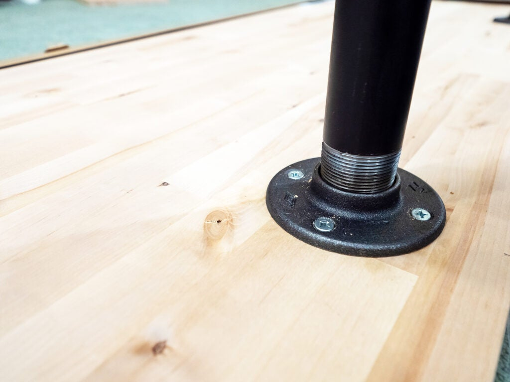 Unscrew three floor flanges and attach them to the underside of your bench top.