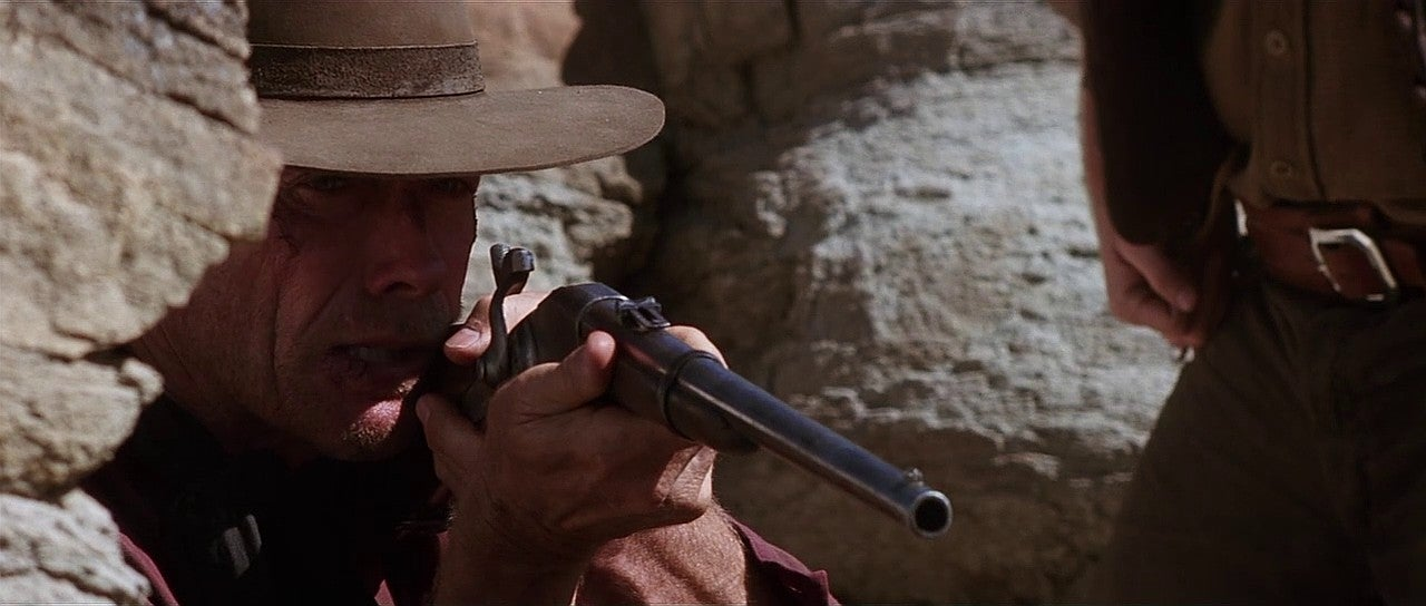 William Munny aiming Ned's Spencer rifle.