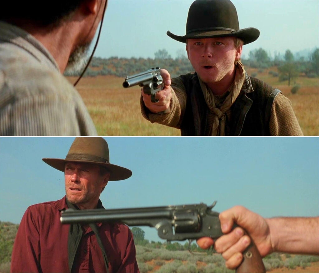 The Kid aims his Schofield top-break revolver at Ned for touching his rifle and calling him blind.