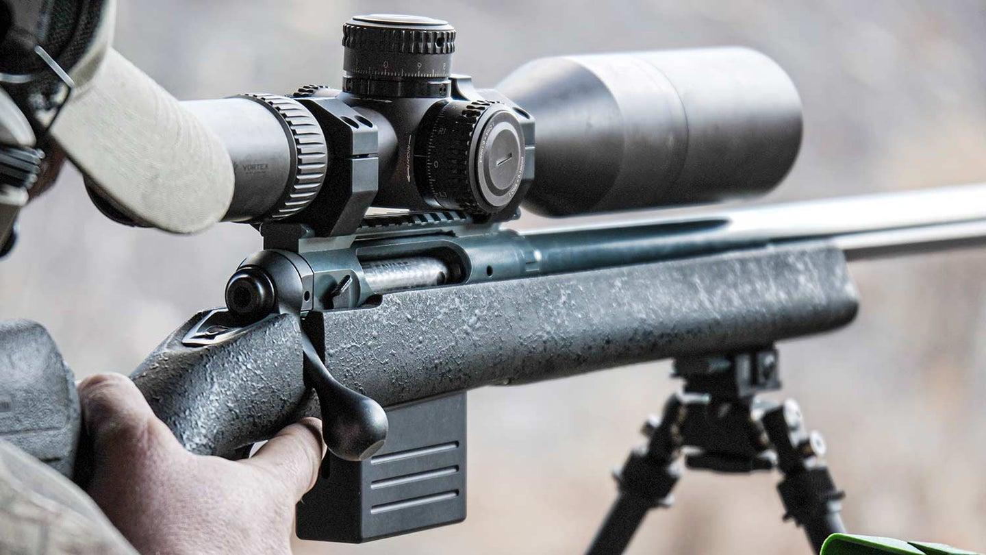 Man aiming a scoped rifle in a range.